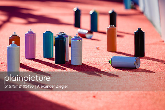 Aerosol cans of spray paint on red carpet - p1579m2193490 by Alexander Ziegler