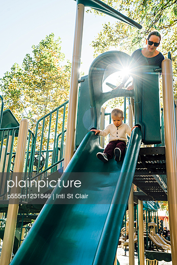 Mother watching son on playground slide - p555m1231846 by Inti St Clair