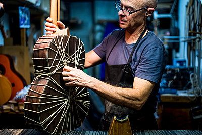 Luthier man making guitars in artisan workshop in Spain. - p1166m2129685 by Cavan Images