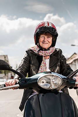 Active senior lady riding motor scooter in the city - p300m2030410 von Uwe Umstätter