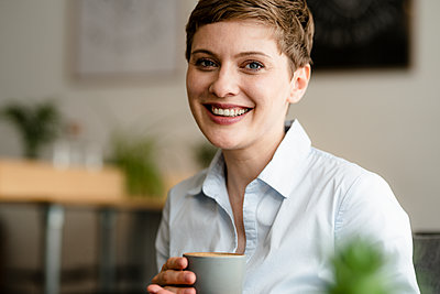 Portrait of happy businesswoman holding cup of coffee - p300m2140839 by Kniel Synnatzschke