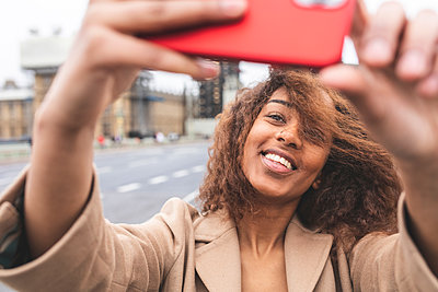 Smiling young woman taking a selfie in the city with Big Ben in background, London, UK - p300m2167643 by William Perugini