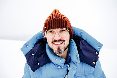 Smiling man with eyeglasses on snow during vacations - p300m2256158 by Katharina Mikhrin