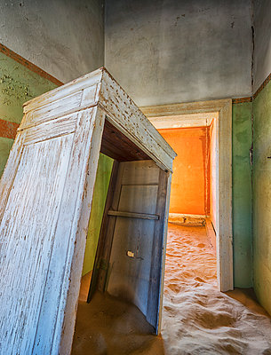 Sand in the rooms of a colourful and abandoned house; Kolmanskop, Namibia - p442m1086780 by Robert Postma