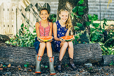 Caucasian girls eating watermelon under tree - p555m1413482 by Inti St Clair