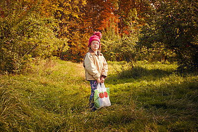 Girl with bag of fresh picked apples in orchard - p924m2091327 by heshphoto