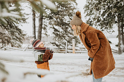 Canada, Ontario, Mother and daughter (2-3) playing with snow - p924m2271194 by Sara Monika