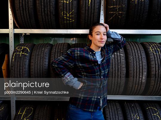 Female mechanic leaning on tire's rack at workshop - p300m2290645 by Kniel Synnatzschke
