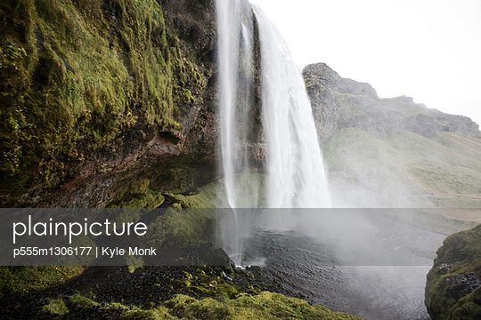 Waterfall over rock formation cliffs - p555m1306177 by Kyle Monk
