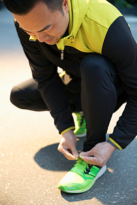 Male runner tying shoelace - p1192m1490309 by Hero Images