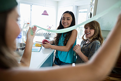 Girl friends making and stretching homemade slime in kitchen - p1192m2009455 by Hero Images