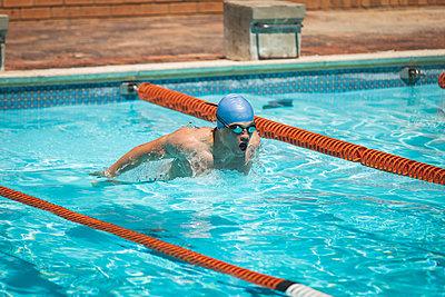 Young Caucasian male swimmer swimming butterfly stroke in swimming pool - p1315m2091022 by Wavebreak