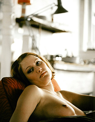 A woman with bare breasts sitting on a couch - p3012804f by fStop