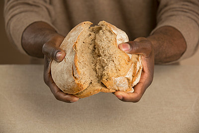 Midsection of man breaking bread loaf at table - p301m1070056f by Paul Hudson
