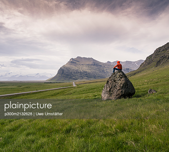 Man sitting on rock in gthe Southern Region, Iceland - p300m2132628 by Uwe Umstätter