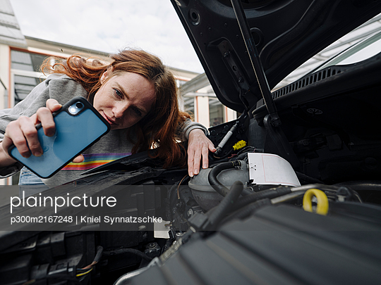 Redheaded woman with cell phone at car - p300m2167248 von Kniel Synnatzschke