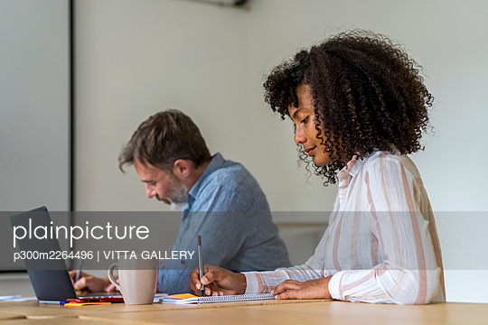 Male and female entrepreneurs preparing strategy during meeting in board room at office - p300m2264496 by VITTA GALLERY