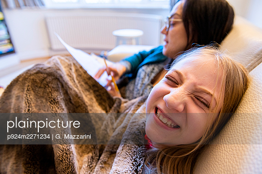 UK, Surrey, Mother and smiling daughter (10-11) on sofa at home - p924m2271234 by G. Mazzarini