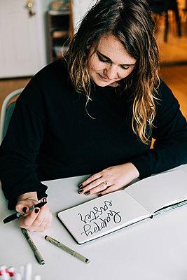 Stock photo of a lettering artist at work with her sketch book. - p1166m2162668 by Cavan Images