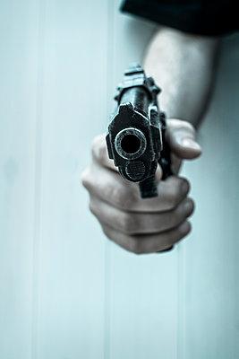 Man with gun close up - p1228m1072164 by Benjamin Harte