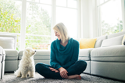 Smiling woman looking at her dog in living room - p300m1537585 by Robijn Page