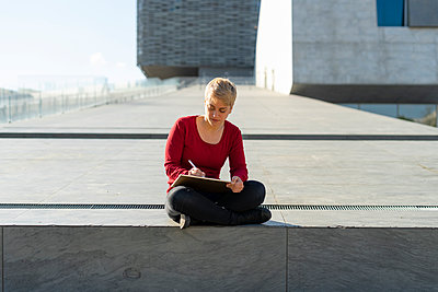 Young freelancer sitting outdoors using digital tablet - p300m2114016 by Francesco Buttitta