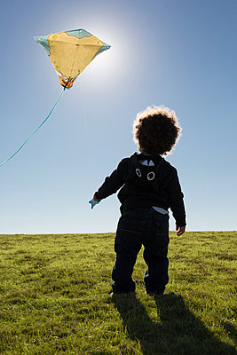 Mixed race boy watching kite flying against blue sky - p555m1419115 by Roberto Westbrook