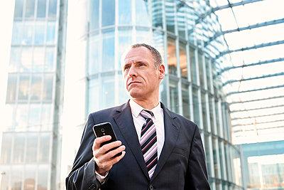 Businessman using mobile phone - p890m1217292 by Mielek