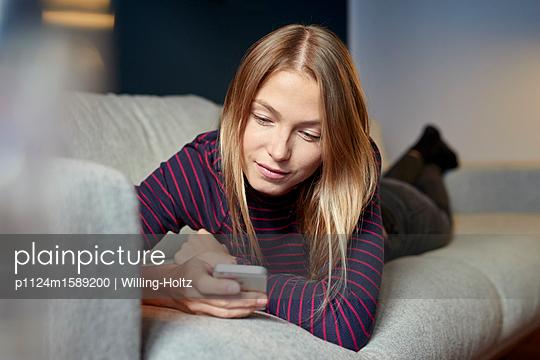 Junge Frau auf dem Sofa mit Smartphone - p1124m1589200 von Willing-Holtz