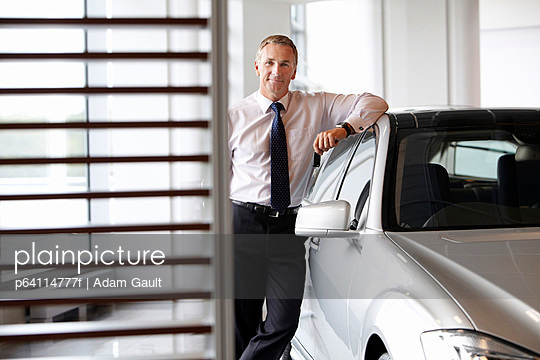 Salesman leaning on new car in showroom