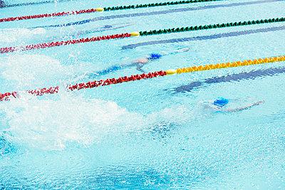 Swimmers racing in pool - p1023m923602f by Paul Bradbury