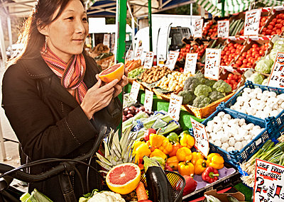 woman shopping at local produce market - p1166m2179556 by Cavan Images