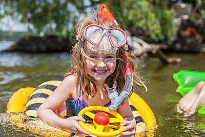 Little girl with swimming ring in lake - p1394m1440847 by benjamin tafel