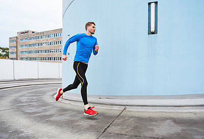 Young man running in the city - p300m1450006 by Daniel Ingold