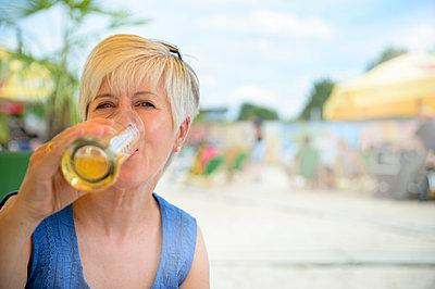 Portrait of senior woman drinking beer at beach bar - p300m2012535 by Frank Röder