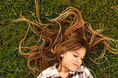 Smiling girl with long hair lying on a meadow - p300m2079674 by Eloisa Ramos
