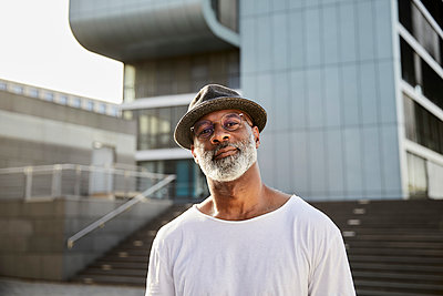 Portrait of smiling mature man with grey beard wearing hat in summer - p300m2131869 by Jo Kirchherr