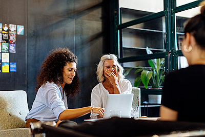 Happy businesswomen with laptop working together in loft office - p300m2144826 by Sofie Delauw