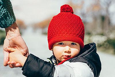 Portrait of little boy wearing red bobble hat - p300m2180838 by Jose Luis CARRASCOSA