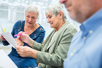 Seniors in therapy group in retirement home writing down notes on sheets of paper - p300m2207048 by Fotoagentur WESTEND61