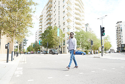 Entrepreneur talking on phone while crossing street in city - p300m2241574 by Pete Muller