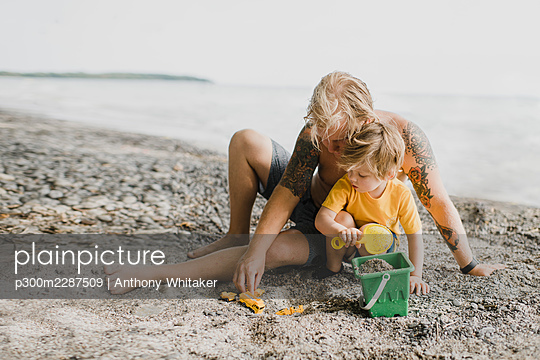 Father and son playing with sand at beach - p300m2287509 by Anthony Whitaker
