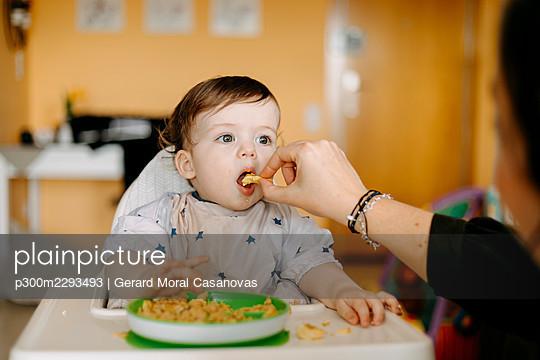Mother feeding son at home - p300m2293493 by Gerard Moral Casanovas