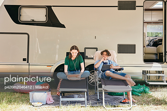 Brother and sister using digital tablet while sitting on folding chairs against motor home - p426m2046412 by Maskot
