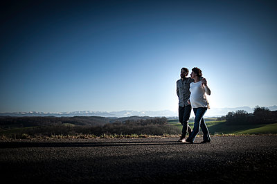 Young couple waiting for a baby walking on a road - p1007m1183434 by Tilby Vattard