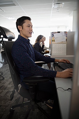 Man working in cubicle at call center - p1192m2040652 by Hero Images