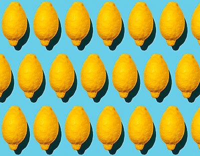 Seamless pattern of ripe lemons against blue background - p300m2198249 by Gemma Ferrando