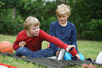 Smiling boys with insulated drink containers while sitting on blanket in park - p301m1180571 by Halfdark