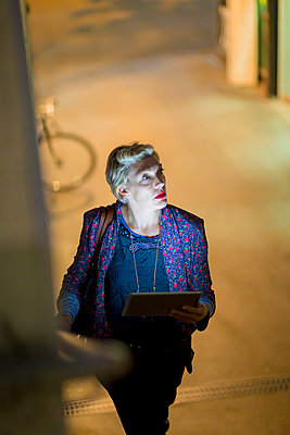 Mature woman using digital tablet on stairway at night, London, UK - p429m999582 by dotdotred