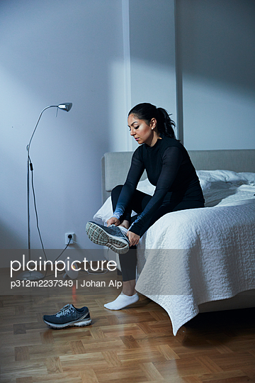 Woman putting shoes on while sitting on bed - p312m2237349 by Johan Alp